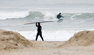 Two surfers ride small waves at the 5th Avenue Beach in Bradley Beach on a chilly day in January 2013.