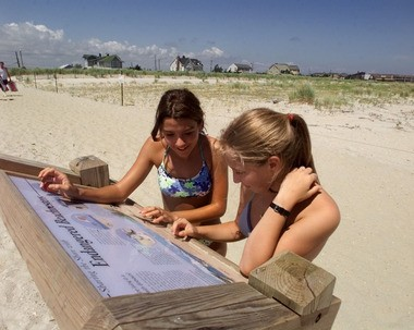 Two sisters look at a sign detailing the endangered birds that share the sand with beachgoers in Monmouth Beach in this file photo.