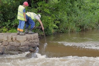 Workmen use a stick to check the height of the water passing over the Nevius Street Dam on the Raritan River before beginning demolition of the dam.