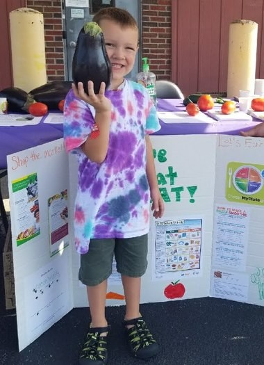 Miles Knight hoists an eggplant at the Precious Times Pennsville preschool farm stand.