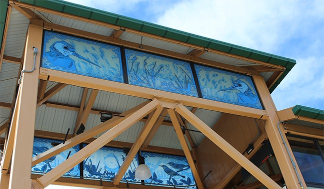 Jenna Lucente's artwork on the railway's towers' glass panels are laminated blue with foreground images of indigenous wildlife and framed with an intricate design that pays homage to neighborhood architecture.