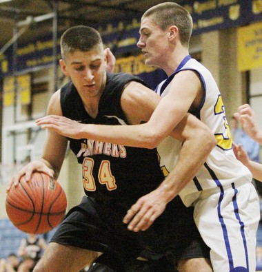 Pitman's Tim Delaney, left, dribbles the ball before turning to the net as Pennsville's Kyle Cranor blocks his shot during Friday's game at Pennsville on Jan. 4, 2013. (Staff Photo by Britney Lillya/South Jersey Times)