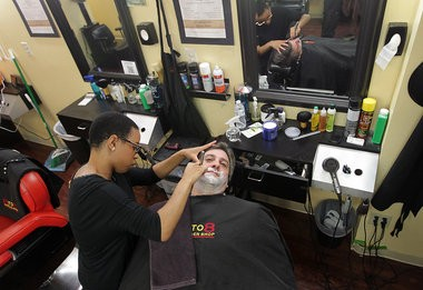 West Orange mayor Robert Parisi gets a shave from Brittany Chiles at 8 to 8 barber shop during a fundraiser for men's health awareness.