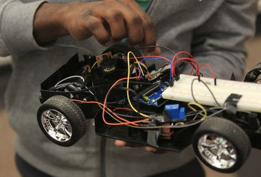 Jean Loizin, 22, checks the car before he demonstrates using brain waves to move the remote controlled car. Essex County College students design car of the future controlled by brain waves, not steering wheel. Members of the Computer Science club use a generic remote controlled car that they move with brain waves.