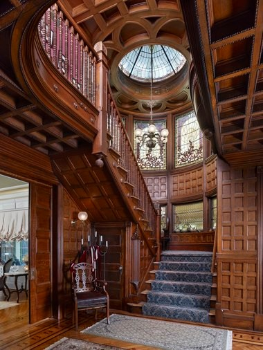 Highly crafted woodwork, coffered ceilings and six foot tall exquisite stained windows set in a turret at the landing of the massive staircase dominate the grand foyer of this magnificent residence. (Photo by J. Stewart)