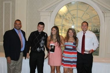 Supervisor of Athletics, Health, and Physical Education Gus Kalikas presents Ali Dugan, John Stauffer, Jessica Sandler, and Andrew Zub with the Frank J. Cicarell Awards.