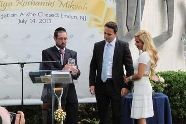 Anshe Chesed Rabbi Joshua Hess presents a plaque to Mark Roshanski and his wife, Kim Azoulay Roshanski, marking the groundbreaking.