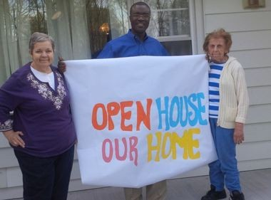 The Community Access Unlimited (CAU) has opened a new Respite Home in Union Township that provides short-term safe and nurturing care to people with disabilities. Pictured, Fanny Sacca (left) and Margaret Rector help assistant program director David Orwochi raise the open house banner at Knollwood, the newly opened Respite Home of Community Access Unlimited. (courtesy photo)