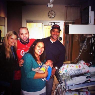 Russell Wilson and his wife Ashton (left), visit with Dave and Kristina Quick and their twin newborns, Harrison (front) and Franklin (rear) in early November.