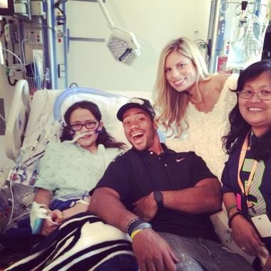 Russell Wilson and his wife, Ashton, visit Allison Christensen and her mother Jovy (far right), shortly after the 11-year old's heart transplant surgery in early October.