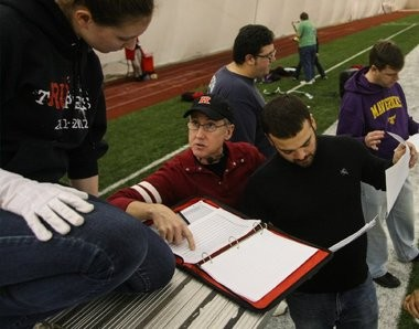 Marching band director Tim Smith, center, works with drum major Lindsey Malko, left, and percussion instructor Carlos Vazquez, right, as the Rutgers University marching band prepares for its Super Bowl show.