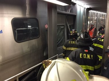 New York City firefighters work on an LIRR train which crashed at Atlantic Terminal Wednesday morning, injuring 100 people. (@FDNY photo)