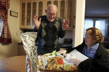 Joe Barbella, 93, of Union, reacts to opening up a Christmas present from Marsha Kreuzman, 90, at his home on Dec. 23.