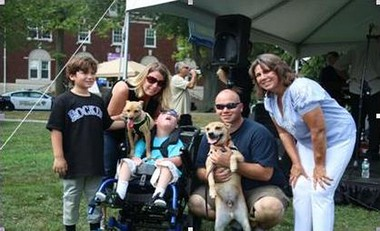 Luke Brown, seated, has a new friend in Turbo, adopted at Home for Good Dog Rescue's Bark-a-Que event in Summit. Standing from left are Luke's brother, Max, parents Felice and Paul Brown, Buddy, and Summit mayor Ellen Dickson.