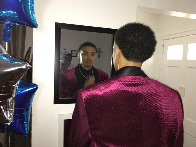 Najeeri Tapia adjusts his necklace as he gets ready to attend the senior prom at St. Mary of the Assumption High School.