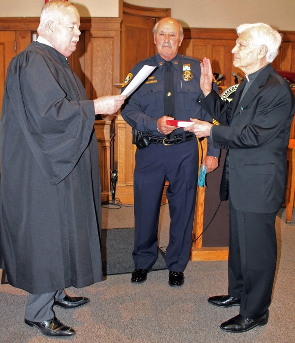 Somerset County Superior Court Judge Michael Rogers (left) swears in the Rev. Joseph Lugo, right, as chaplain to the Somerset County Sheriff's Office. Sheriff Frank Provenzano holds the Bible. (courtesy photo)