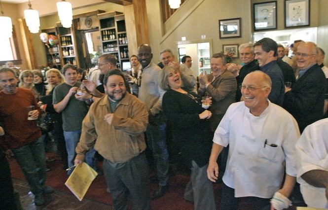 Customers and staff applaud Tommy Mandina (right) in the main dining room in February 2007, during the first lunch service at the restaurant following Hurricane Katrina.