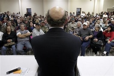 In this Jan. 10, 2011 photo, claimants listen to BP oil spill fund administrator Kenneth Feinberg, center, as he speaks at a town hall meeting in Grand Isle. In court filings late Monday the oil giant BP asked a federal judge to disregard objections from a fraction of claimants and give final approval to a proposed multibillion-dollar settlement for economic damages from the Gulf spill.