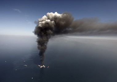 In this Wednesday, April 21, 2010 file photo, oil can be seen in the Gulf of Mexico, more than 50 miles southeast of Venice on Louisiana's tip, as a large plume of smoke rises from fires on BP's Deepwater Horizon offshore oil rig. A federal appeals court on Monday, May 19, 2014, refused to reconsider its previous ruling that businesses don't have to prove they were directly harmed by BP's 2010 Gulf Of Mexico oil spill to collect settlement payments.