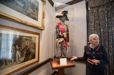 Phyllis Taylor shows a replica uniform ensemble of Vice Admiral Horatio Nelson at the Lee Circle headquarters of the Patrick F. Taylor Foundation.