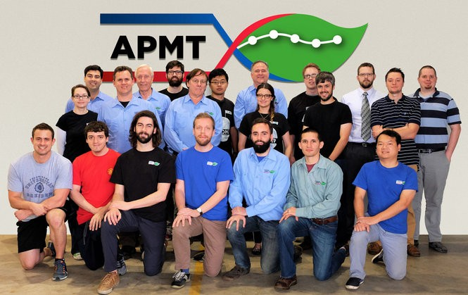 The APMT team led by CEO Alex Reed, top row far left, develops polymer monitoring equipment for plastics makers and other chemical manufacturers. The company has also developed a light-scattering tool to help drug makers quickly test the stability of drug formulas. (Photo courtesy APMT)