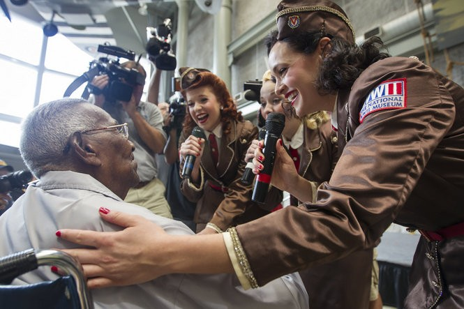 World War II veteran Lawrence Brooks, 107, is treated to singing, hugs, and kisses from Andrea Pizza, right, Dody Piper, back right, and Mandi Ridgdell, back center, performers with The National World War II Museum's Victory Belles. (Photo by Chris Granger, Nola.com | The Times-Picayune)