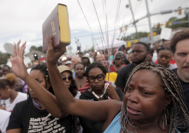 People gather for a vigil for Alton Sterling at the Triple S Food Mart in Baton Rouge, Wednesday, July 6, 2016. Sterling was shot dead by Baton Rouge Police at the food mart on Tuesday (July 5). (Photo by Brett Duke, Nola.com | The Times-Picayune)