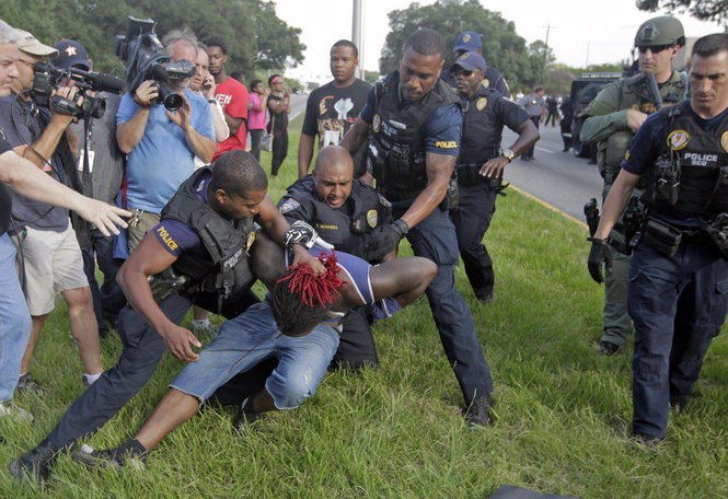 A man is detained by law enforcement as demonstrators protest the shooting death of Alton Sterling outside the Baton Rouge Police Department headquarters on Saturday, July 9, 2016. (Photo by Brett Duke, Nola.com | The Times-Picayune)