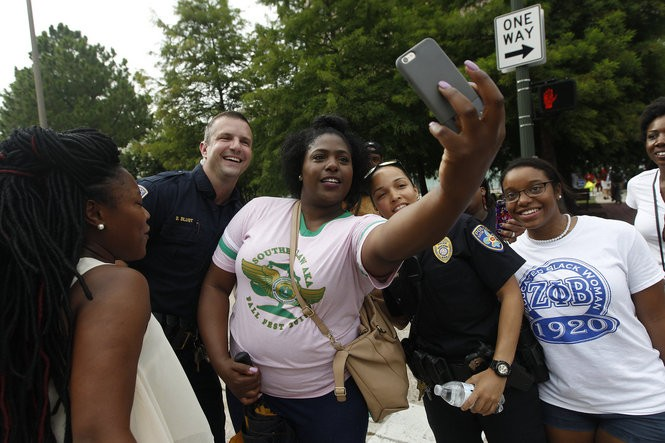 Protesters take selfies with Baton Rouge Police during their march toward the state capitol in Baton Rouge on Sunday, July 10, 2016, days following the Alton Sterling shooting. (Photo by Chris Granger, Nola.com | The Times-Picayune)