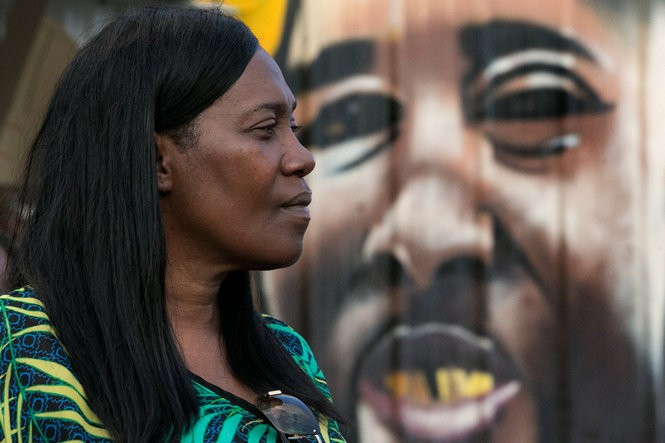 Sandra Sterling, the aunt of Alton Sterling that many refer to as his mother claps stands in front of a painted mural as her church family gathers for a service in the parking lot of Triple S Food Mart on North Foster Drive in Baton Rouge on Wednesday. (Photo by Ted Jackson, Nola.com | The Times-Picayune)