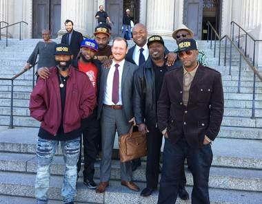 Defense attorneys Robert Hjortsberg and Jason Williams, center, celebrate with supporters outside the New Orleans criminal courthouse after the perjury acquittal Monday (Jan. 30) of Hakim Shabazz, lower right, and Kevin Johnson, far lower right.