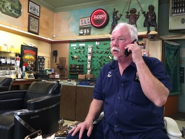 Covington cigar store owner Patrick Clanton takes a phone call Friday (May 19). Clanton scribbles his musings on a sign he places in front of the store, and on Tuesday (May 16) that sign was stolen.