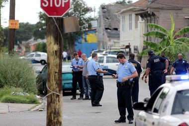 Members of the New Orleans Police Department investigate a fatal shooting at the corner of Mandeville and N. Derbigny Streets on Saturday, July 27, 2013.