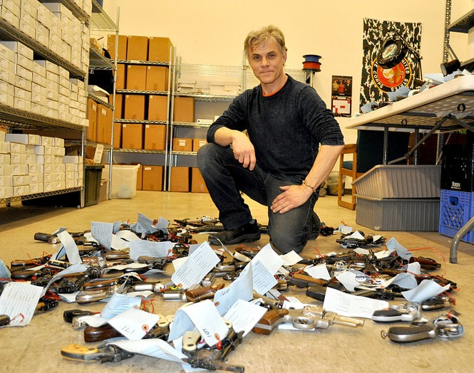 Artist Brian Borrello among the confiscated weapons used in the 'Guns in the Hands of Artists' exhibit (Photo courtesy Brian Borello)
