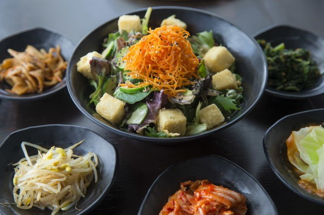 The fried tofu salad at Little Korea on Magazine Street in New Orleans features organic mixed greens, peanut dressing, marinated zucchini, sesame, and shredded carrots. It is surrounded by bowls of banchan on Monday, February 19, 2018.