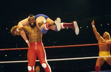 Mr. T lifts Roddy Piper as Hulk Hogan cheers his partner on.