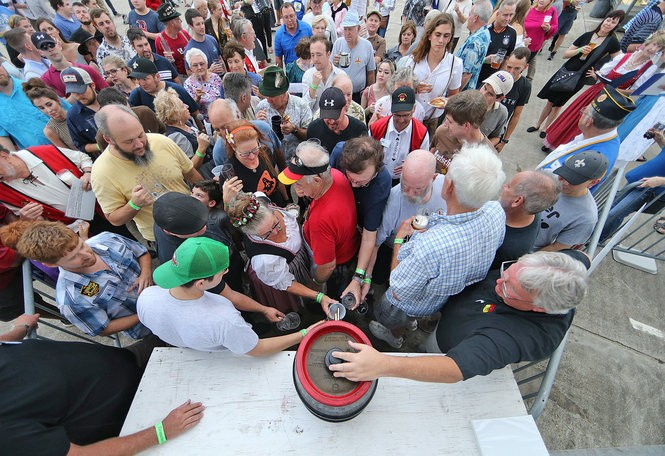 Beer lovers fill their glasses from the ceremonial first keg during the Deutsches Haus Oktoberfest, the three-weekend festival in October celebrating German culture, food, beer, wine, oompah music and dancing on Friday, October 6, 2017. (Photo by Michael DeMocker, NOLA.com | The Times-Picayune)