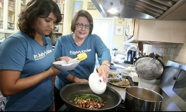 Diya Chacko and Judy Walker add parsley as they rewarm the almond topping for Trout Amandine.