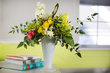 """Designed by Denise Richter and Megan McHugh of Pistil & Stamen Flower Farm, this arrangement features rieger begonias, nandina foliage, jonquils, camphor leaves and berries, and magnolia foliage in a white milk-glass vase. """"We wanted to go for an almost-spring look with this one,"""" Richter said. """"We chose a light vessel, a cheerful color palette and lighter textural elements, like the nandina foliage to keep it bright and airy."""""""