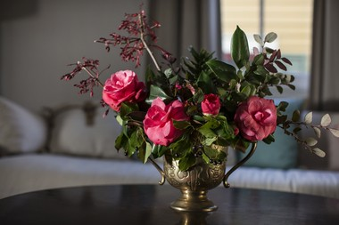 """This arrangement by Pistil & Stamen features camellias, magnolia foliage, loropetalum, flowering red maple branches and fern frond in a gold urn. """"We wanted to let this one shine in its opulence and formality,"""" Richter said. """"We chose a substantial gold vessel to balance the lush richness of the camellias and magnolia foliage. To give movement to the arrangement, we used the smaller leaves of loropetalum and the flowering bare branches of red maple."""""""