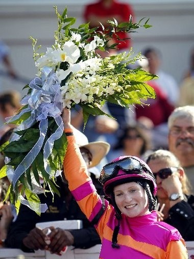 Rosie Napravnik poses for a photo in the winner's circle after riding Pants on Fire to victory in the 98th running of the Louisiana Derby at the Fair Grounds on March 26, 2011. Napravnik was the first female jockey to win the race.