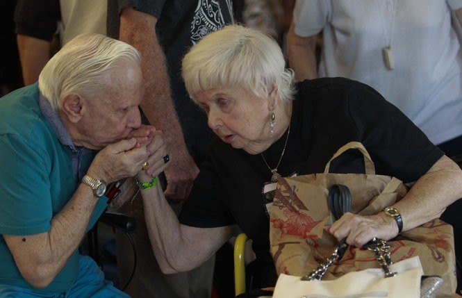 Donald Baylis, left, kisses Rosalyn Dobson's hand before getting on buses at the Brookdale Margate assisted-living facility west of Fort Lauderdale, Florida, which evacuated to Bradenton on Friday before the arrival of Hurricane Irma. (Photo by Andrew Innerarity for The Washington Post)