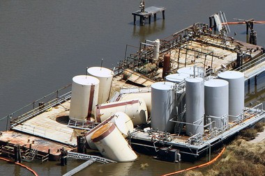Toppled oil storage tanks near the town of Lafitte after Hurricane Isaac in 2012. The tanks toppled off of their foundations and into the water, causing oil to spill into nearby wetlands. (Photo by Jonathan Henderson, Gulf Restoration Network)