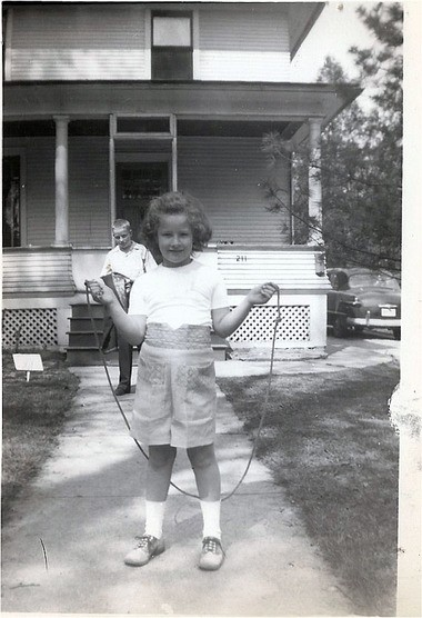 Sheila Stroup (then Sheila Tierney) jumping rope in front of the house her grandfather had built in 1906. Her big brother Larry Tierney is behind her.
