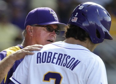 LSU coach Paul Mainieri, left, talks with Kramer Robertson last season in an NCAA Regional game.