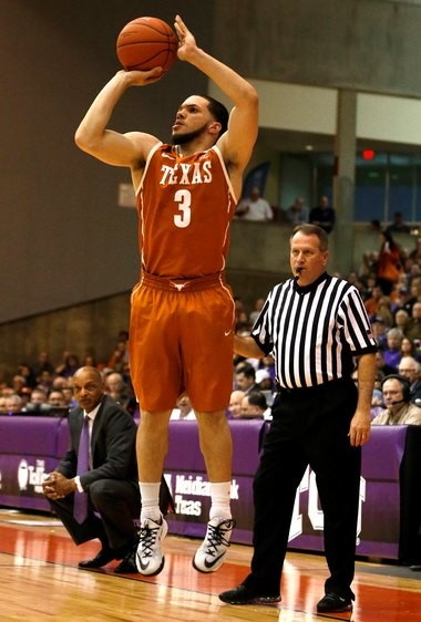In a picture dripping with irony, former St. Augustine star Javan Felix rises up for a 3-point jump shot against TCU as former LSU coach Trent Johnson looks on earlier this season. Perimeter shooting has been Felix's specialty this season for the Longhorns.