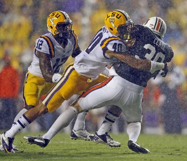 LSU Tigers linebacker Duke Riley (40) brings down Auburn Tigers punter Steven Clark (30) in Baton Rouge Saturday, September 21, 2013. Riley excelled on special teams for three years with LSU.