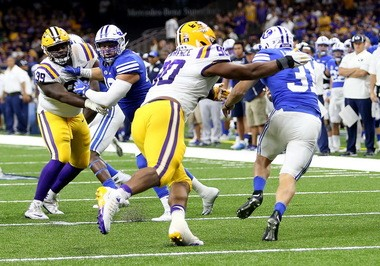 LSU's defense is not the same when end Rashard Lawrence (90), seen here tackling BYU punter Jonny Linehan (31) on a failed fake punt, isn't on the field.