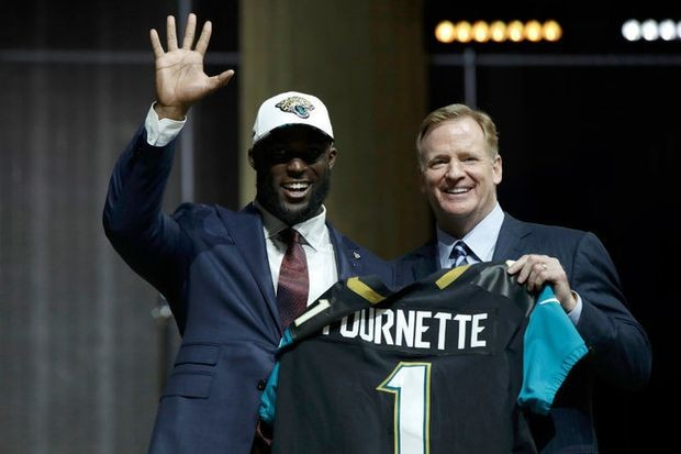LSU's Leonard Fournette, left, waves as he poses with NFL commissioner Roger Goodell after being selected by the Jacksonville Jaguars during the first round of the 2017 NFL football draft, Thursday, April 27, 2017, in Philadelphia. (Matt Rourke/The Associated Press