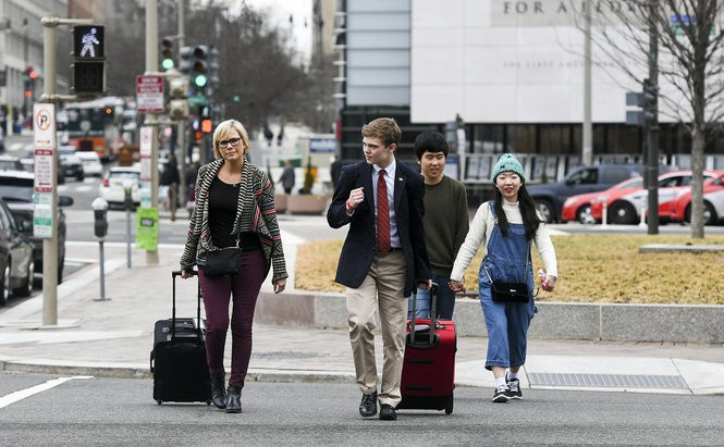 Tyler Ruzich crosses Pennsylvania Avenue in Washington with his mother, Carrie Stracy, after recording a news interview at the Newseum. (Photo by Jonathan Newton, The Washington Post)
